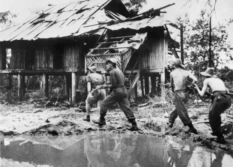 A_British_infantry_patrol_cautiously_approaches_a_damaged_building_in_a_Burmese_village_1944._SE141.jpg